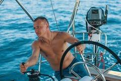 Homem novo ao leme de um iate da navigação passatempo fotos de stock royalty free