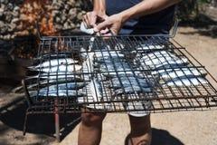 Homem novo aproximadamente para grelhar sardinhas Fotos de Stock