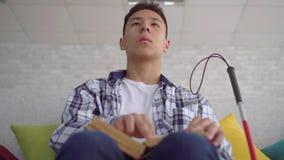 Homem novo asiático cego que lê um livro do texto do braile que senta-se no sofá no fim da sala de visitas acima filme