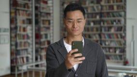 Homem novo asiático com o telefone que texting no fundo das estantes video estoque