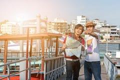 Homem novo asiático da trouxa como um turista que olha o travell do mapa fotografia de stock