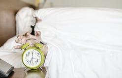 Homem novo asiático de sono perturbado no amanhecer do despertador foto de stock