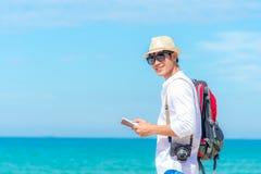 Homem novo asiático de sorriso feliz do turista caucasiano que olha o passaporte com a câmera na praia foto de stock