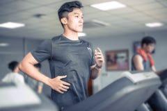 Homem novo asiático no sportswear que corre na escada rolante no gym | Esporte saudável da atividade imagem de stock royalty free