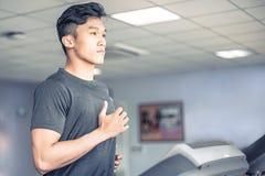 Homem novo asiático no sportswear que corre na escada rolante no gym | Esporte saudável da atividade fotos de stock royalty free