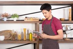 Homem novo asiático que veste o avental marrom usando a tabuleta imagem de stock