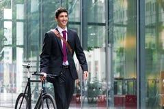 Homem novo ativo feliz que anda ao trabalho após o commutin da bicicleta fotografia de stock