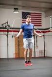 Homem novo atlético apto que usa uma corda de salto fotos de stock royalty free