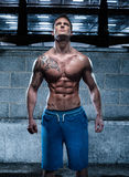 Homem novo atlético considerável com a tatuagem que olha acima foto de stock