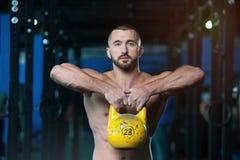 Homem novo atlético descamisado que levanta Kettlebell nas mãos foto de stock royalty free