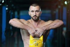 Homem novo atlético descamisado que levanta Kettlebell nas mãos imagem de stock royalty free