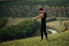 Homem novo atlético no sportswear que faz exercícios com mãos levantadas e que olha para baixo no fundo da paisagem da natureza imagens de stock royalty free