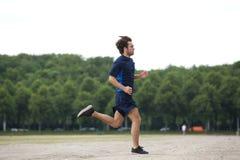 Homem novo atlético que corre fora imagem de stock royalty free