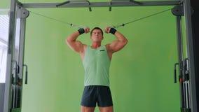 Homem novo atlético que dá certo no equipamento do exercício da aptidão no gym filme