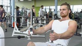 Homem novo atlético que exercita em um dispositivo de bloco Retrato do homem atlético forte no treinamento do gym fotografia de stock royalty free
