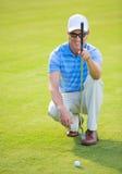 Homem novo atlético que joga o golfe Imagens de Stock