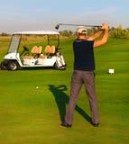 Homem novo atlético que joga o golfe Fotografia de Stock