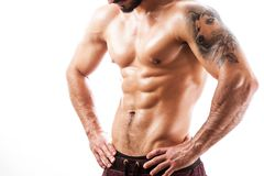 Homem novo atlético que olha o seu abdominal fotos de stock royalty free