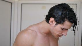 Homem novo atlético que toma o chuveiro na praia filme