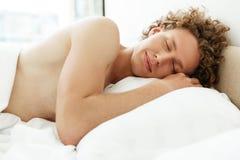 Homem novo atrativo com cabelo encaracolado que dorme na cama Fotografia de Stock