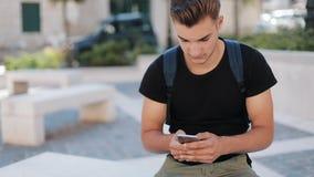 Homem novo atrativo com uma trouxa usando o telefone que senta-se no fim ocupado do retrato da tecnologia velha da cidade acima d video estoque