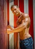 Homem novo atrativo do músculo que inclina-se contra vestiário coloridos da praia Fotografia de Stock Royalty Free