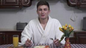 Homem novo atrativo em um roupão branco que senta-se na mesa de cozinha que aprecia o aroma da placa do café da manhã com fritado vídeos de arquivo