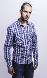 Homem novo atrativo em uma camisa de manta Imagem de Stock