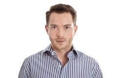 Homem novo atrativo na camisa azul que olha fixamente na câmera Imagem de Stock