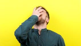 Homem novo atrativo na camisa ocasional que boceja na câmera video estoque