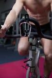 Homem novo atrativo na ginástica na bicicleta Imagens de Stock