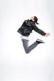 Homem novo atrativo no casaco de cabedal preto que salta altamente Fotografia de Stock