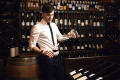 Homem novo atrativo no terno branco e calças que degustating o vinho tinto fotografia de stock royalty free