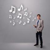 Homem novo atrativo que canta e que escuta a música com musical Fotografia de Stock Royalty Free