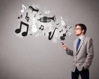 Homem novo atrativo que canta e que escuta a música com musical Imagens de Stock