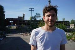 Homem novo atrativo que está exterior na frente da casa abandonada, olhando a câmera Detroit recolhido foto, Michigan imagem de stock