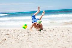 Homem novo atrativo que joga o voleibol na praia Foto de Stock
