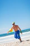 Homem novo atrativo que joga o voleibol na praia Imagens de Stock Royalty Free