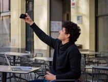 Homem novo atrativo que usa o telefone celular esperto que fica conectado ao viajar em torno de Europa imagem de stock