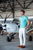 Homem novo atrativo sério que está na frente dos aviões pequenos Fotografia de Stock Royalty Free