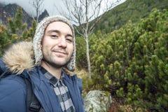 Homem novo aventuroso nas montanhas durante o tempo frio fotografia de stock