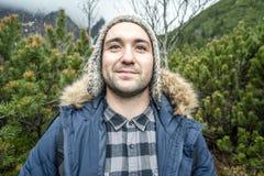Homem novo aventuroso nas montanhas durante o tempo frio foto de stock