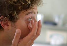 Homem novo bem parecido que aplica a lente de contato fotografia de stock royalty free