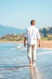 Homem novo bem sucedido que anda ao longo de uma praia Imagens de Stock Royalty Free