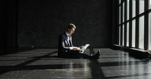 Homem novo bem sucedido que trabalha no escritório domiciliário no estilo do sótão Homem à moda do moderno em um terno que trabal filme