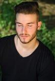 Homem novo calmo com os olhos fechados, relaxando fora na natureza Foto de Stock