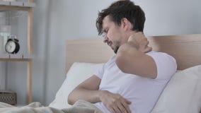 Homem novo cansado com a dor de pescoço que senta-se na cama video estoque
