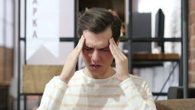 Homem novo cansado com enxaqueca da dor de cabeça sobre o fundo do escritório video estoque