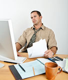 Homem novo cansado em contas pagando da mesa Fotos de Stock Royalty Free