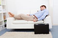 Homem novo cansado no sofá Fotografia de Stock Royalty Free